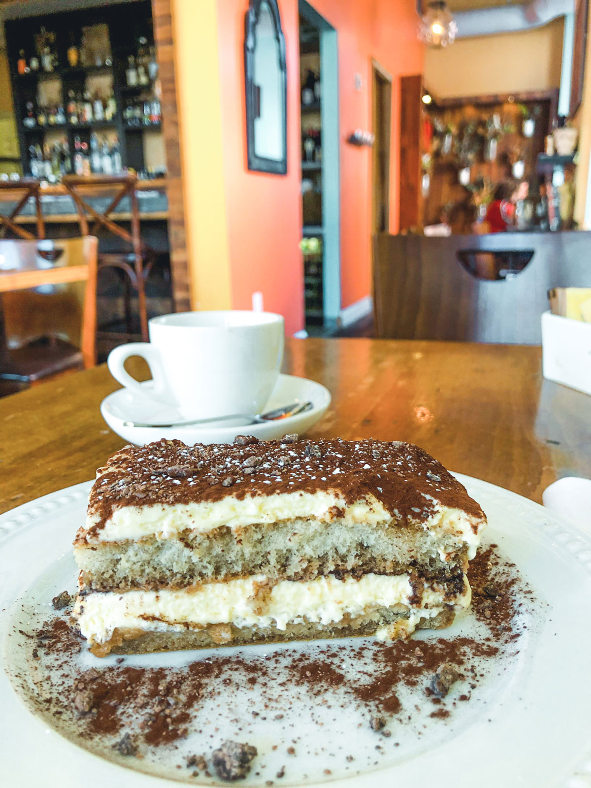 A slice of tiramisu resting on a white dish.