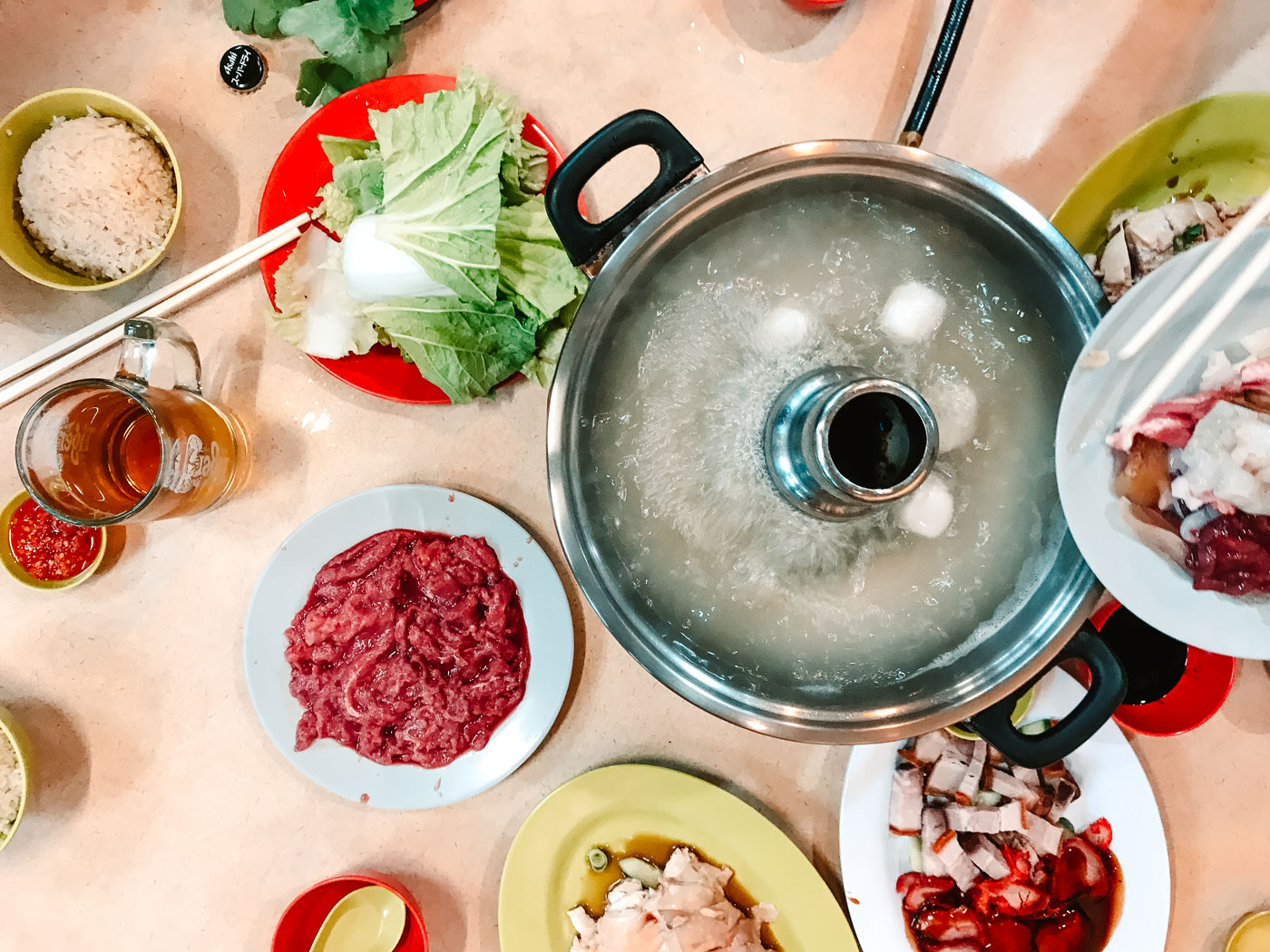 A boiling steamboat surrounded by raw vegetables and meats.