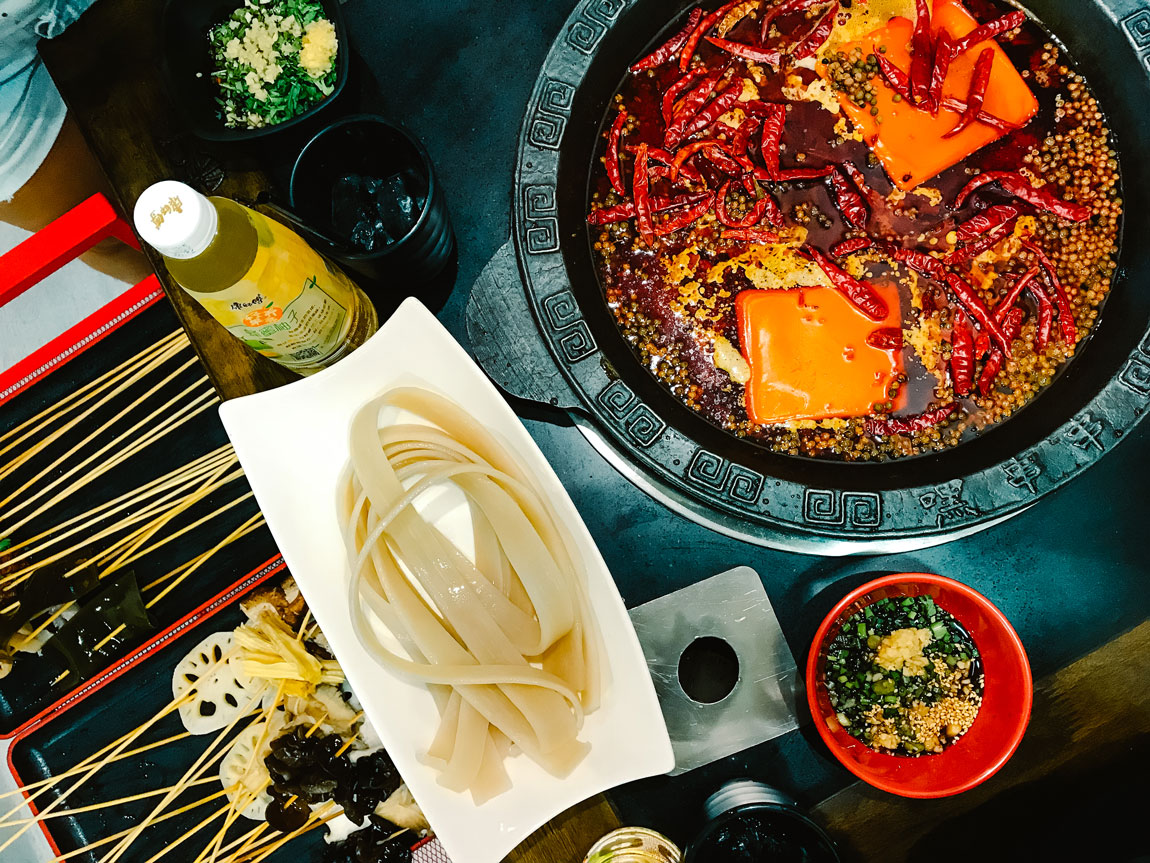 A white dish holding noodles next to a spicy steamboat.