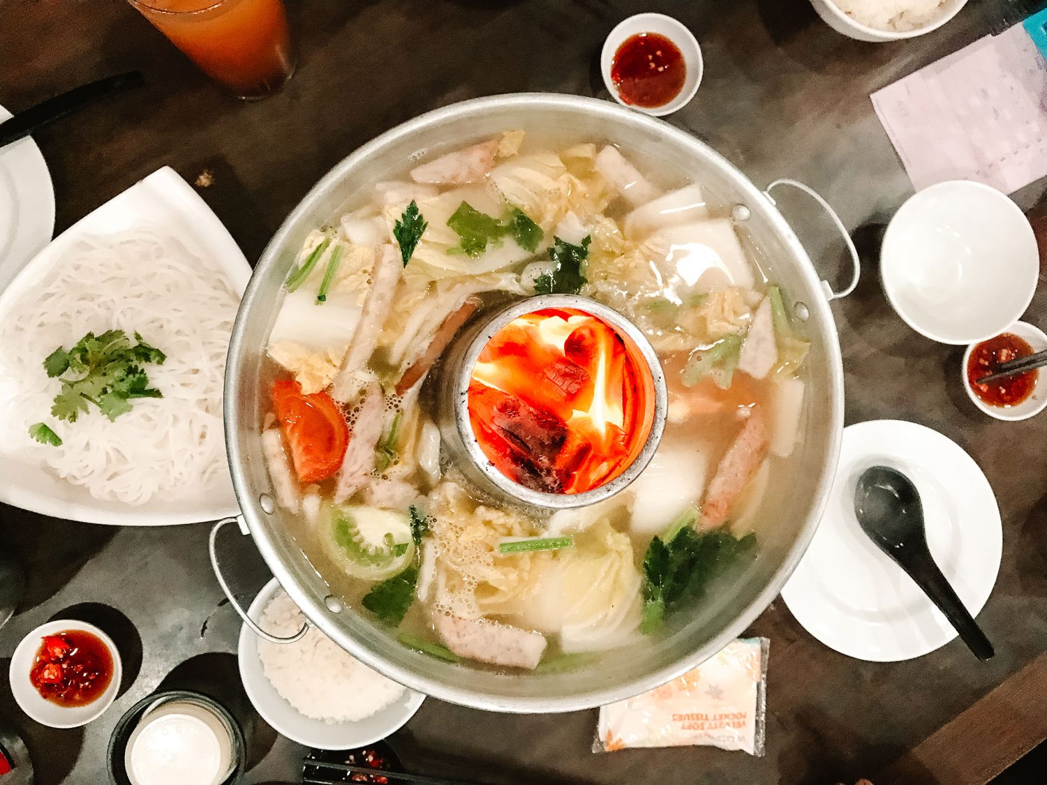 A large non-spicy steamboat in the center of the table.