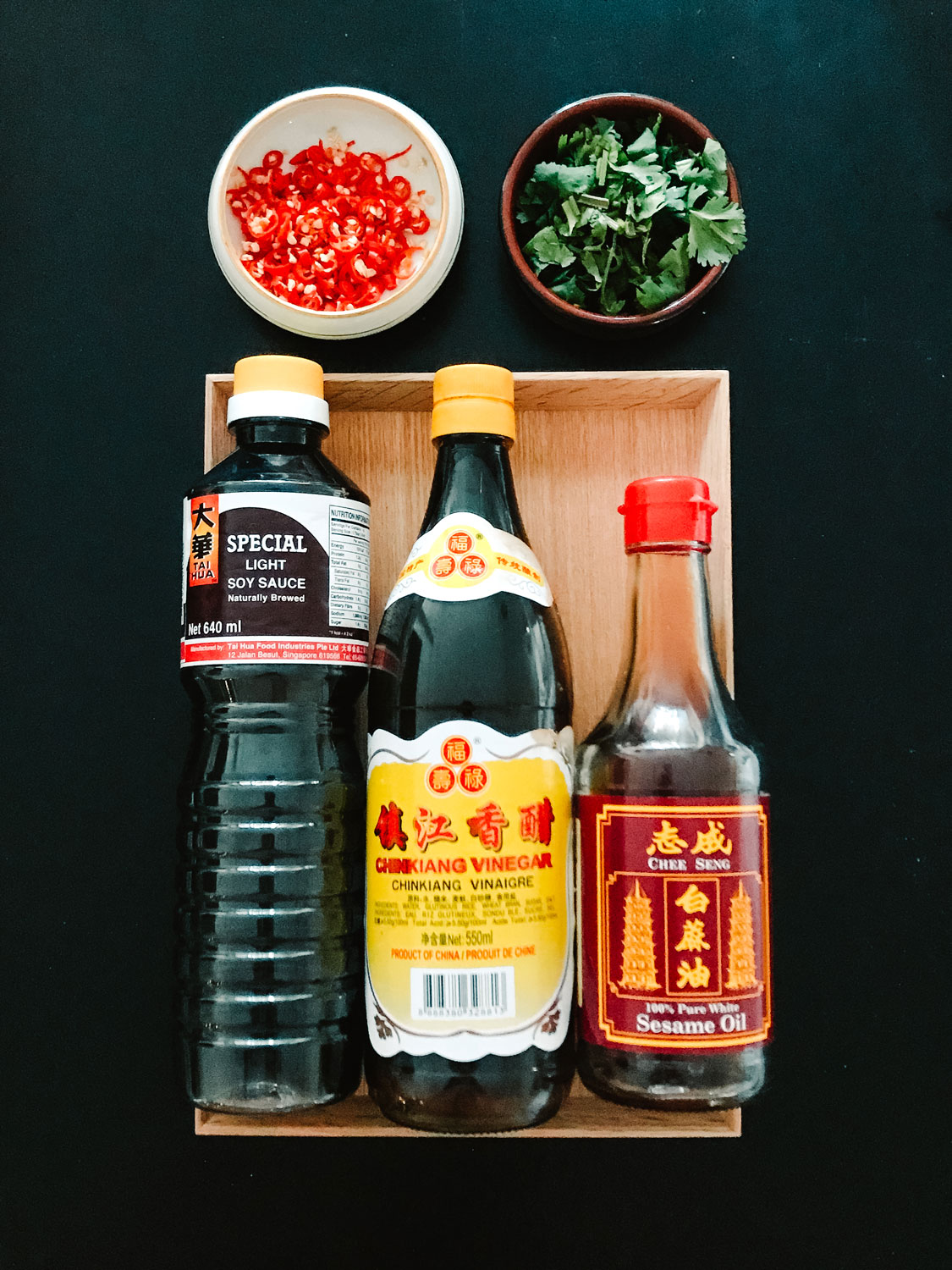 A bottle of sesame oil, soy sauce and black vinegar with small dishes of chili rings and coriander.