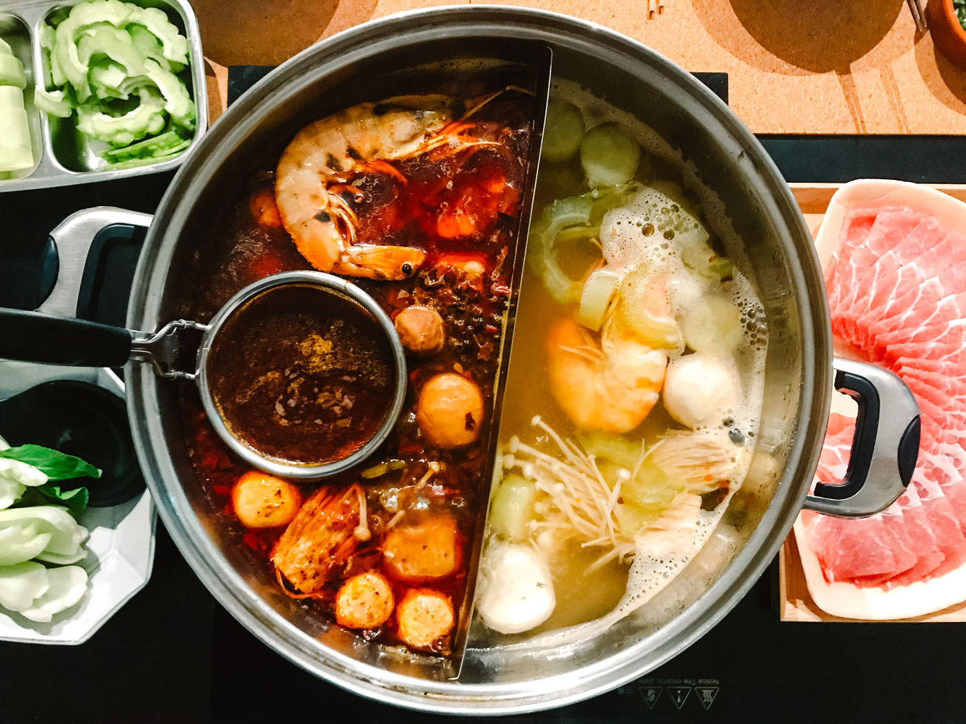 A steamboat, or hotpot, resting on a table with various raw ingredients.