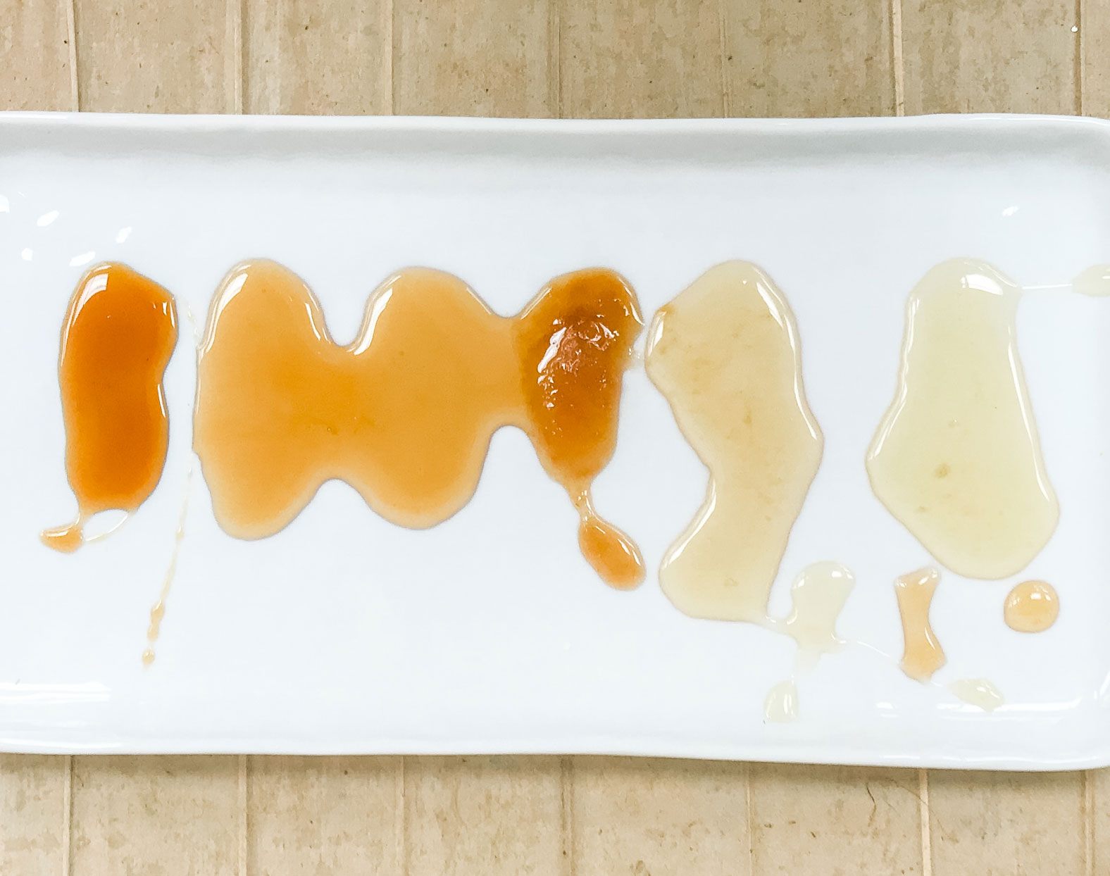 A large white dish of different types of honey.