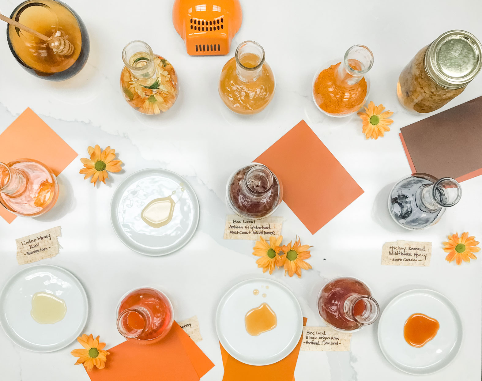 Several bottles of honey accompanied by their select dishes.