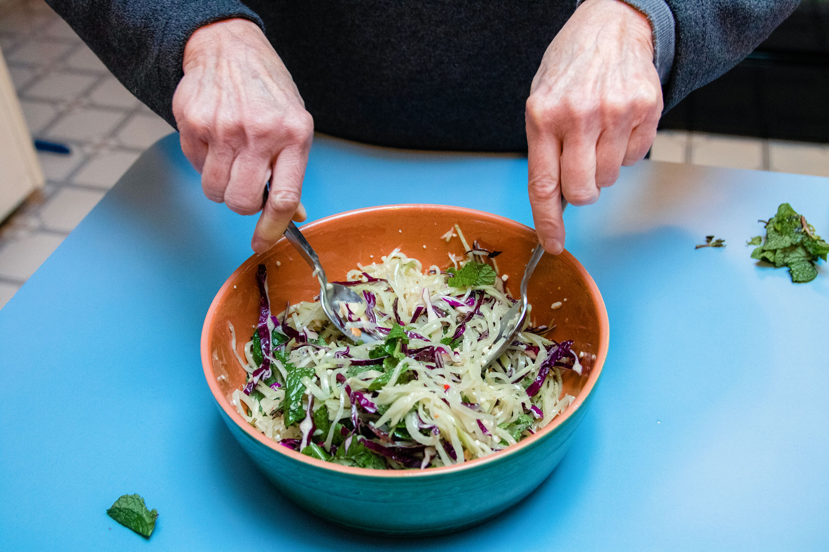 A person mixing together Spicy Green Papaya Slaw from Myers + Chang.