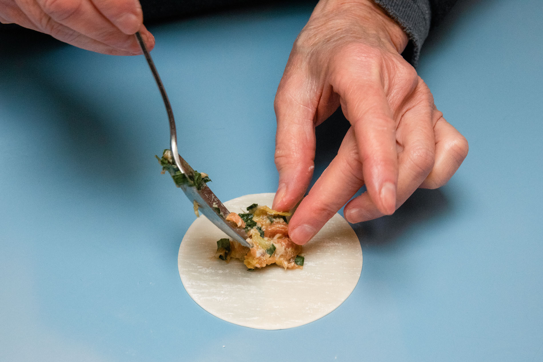 A person gently placing filling into a dumpling wrapper.