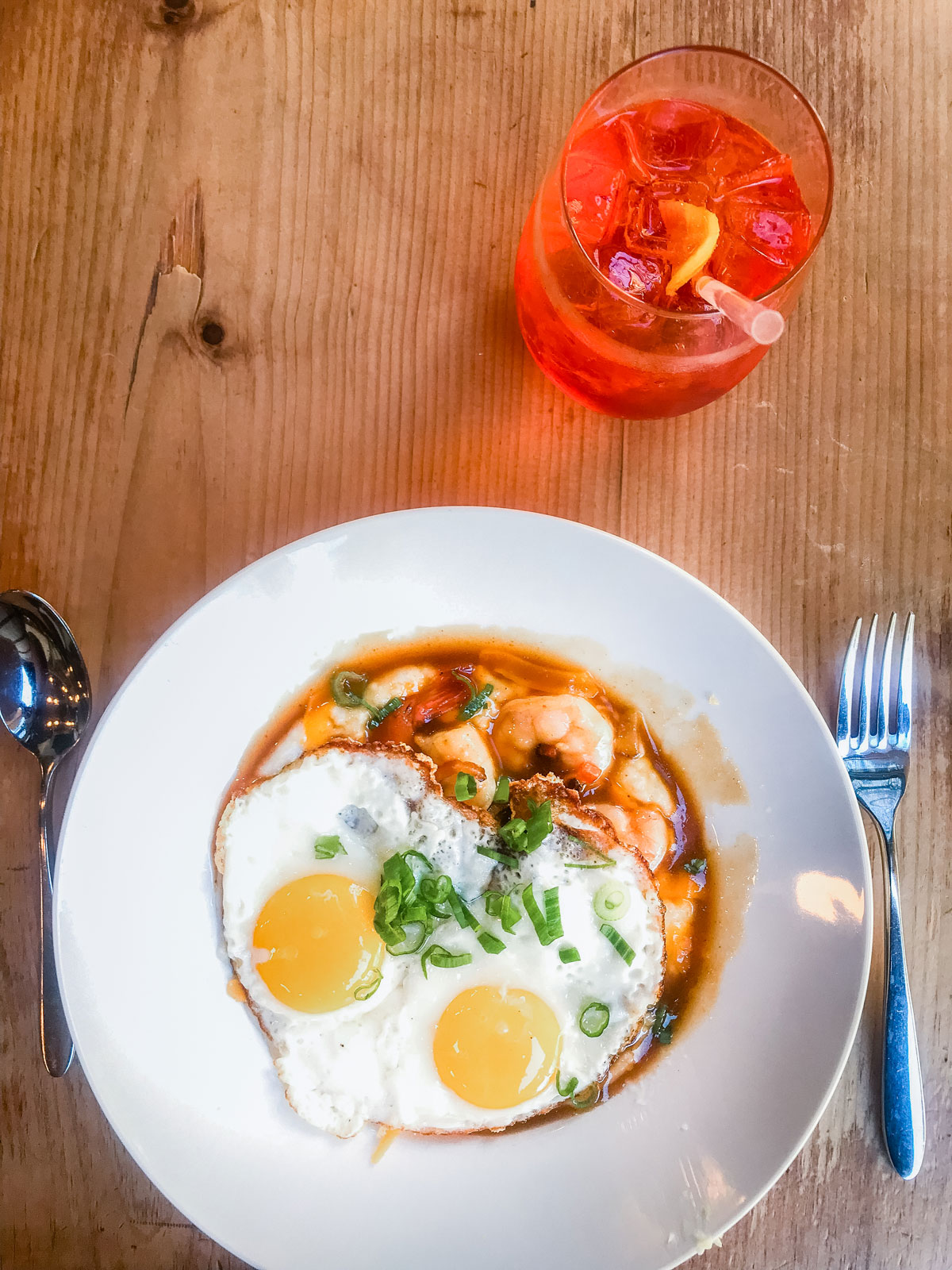 A fried egg resting on top of a bowl of shrimp and grits.
