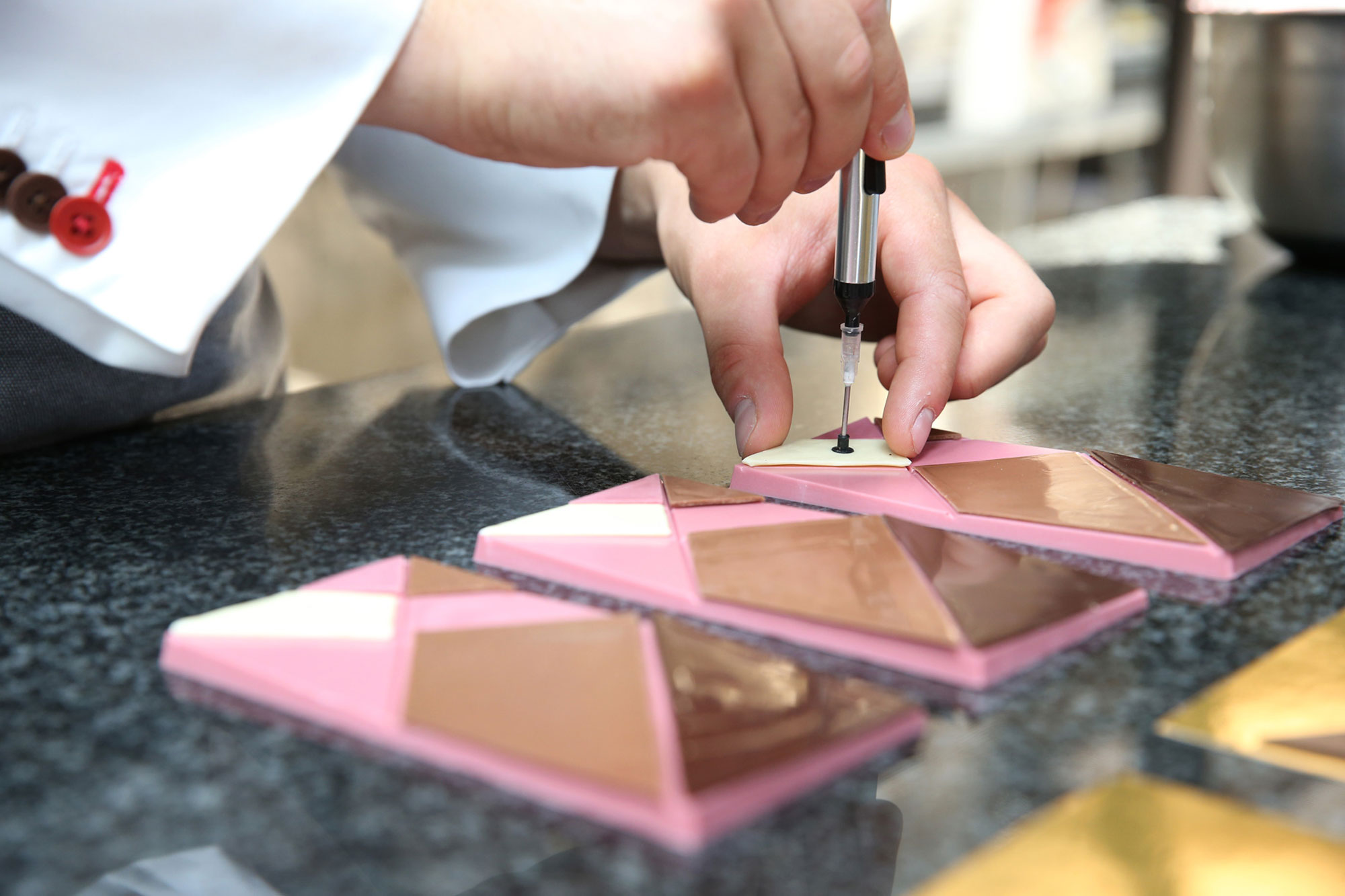 A chef putting together a four-chocolate bar.