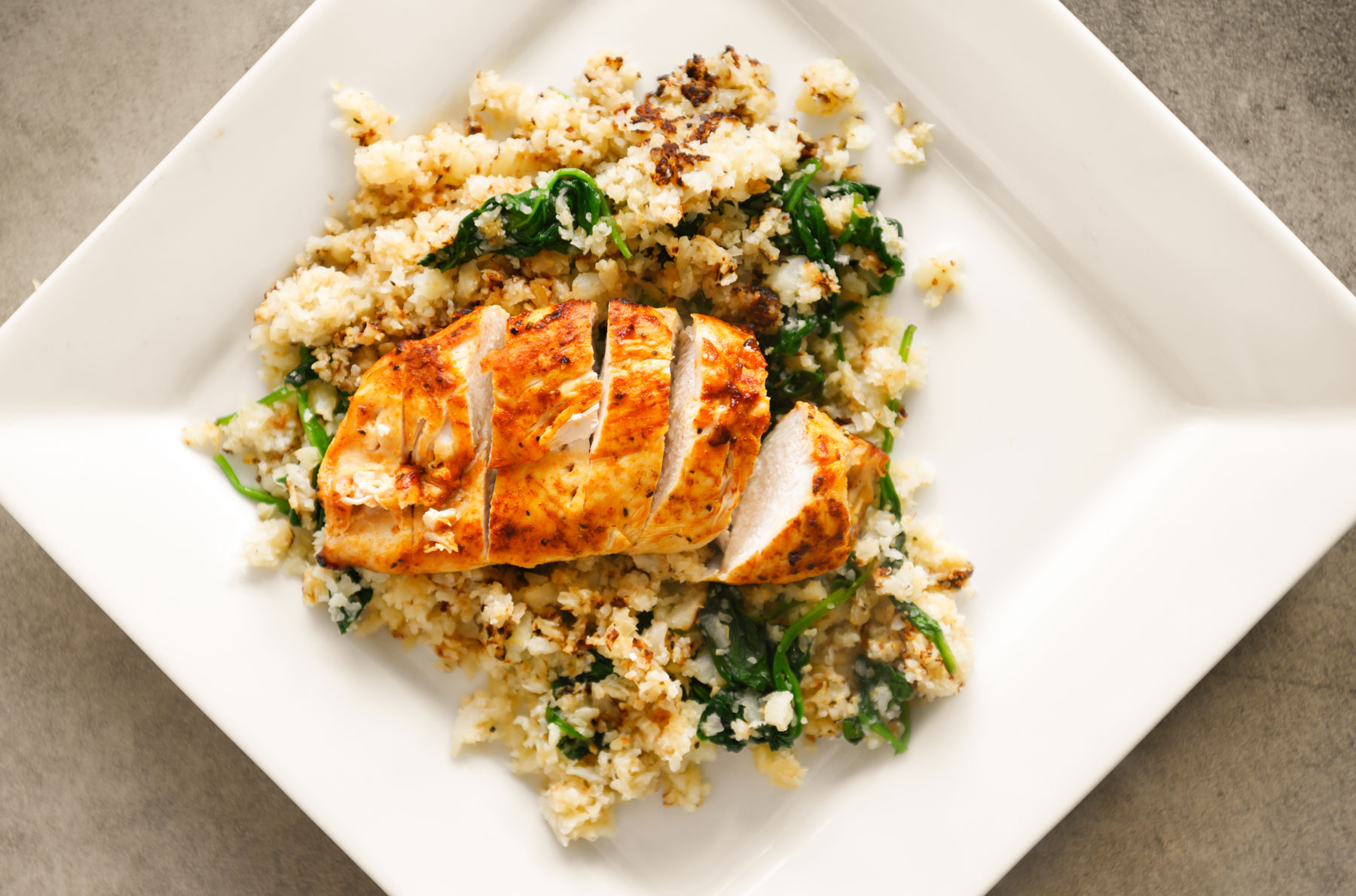 Sliced chicken resting on a bed of cauliflower rice.