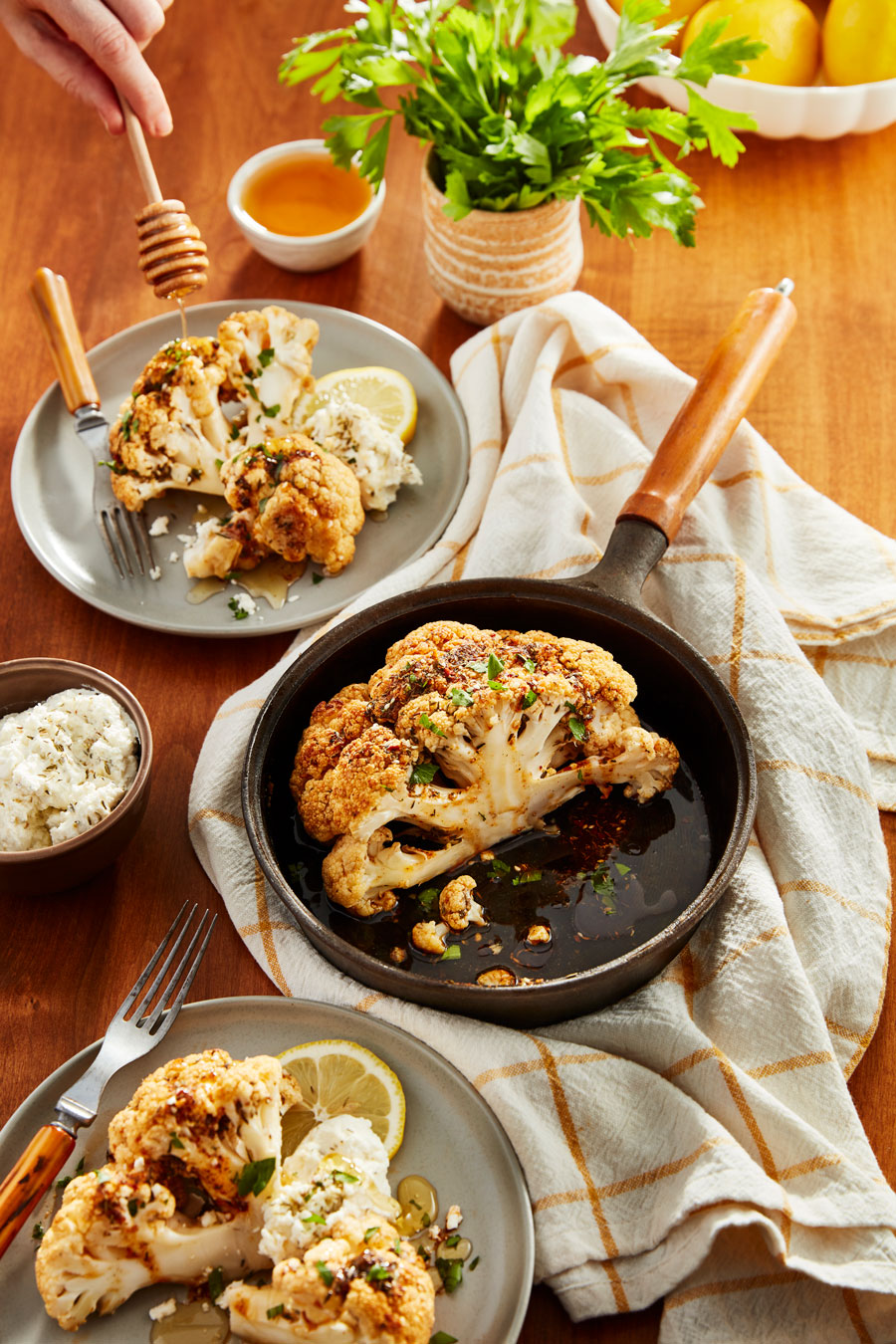 A skillet of roasted cauliflower surrounded by served plates.