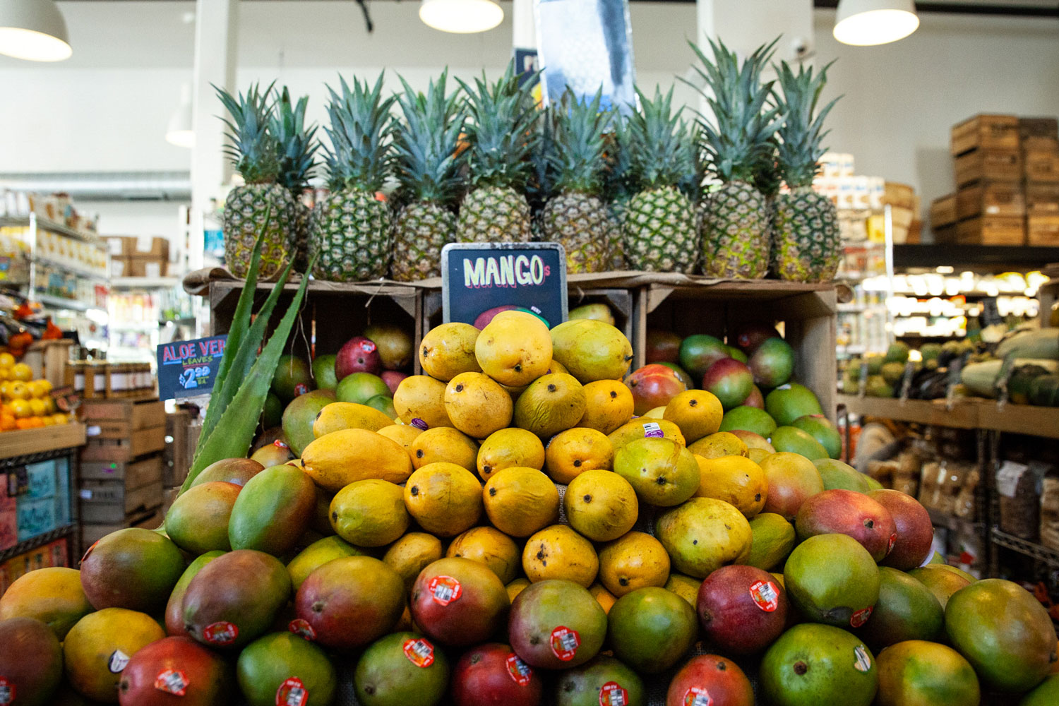 Piles of mangoes and pineapples out on display.