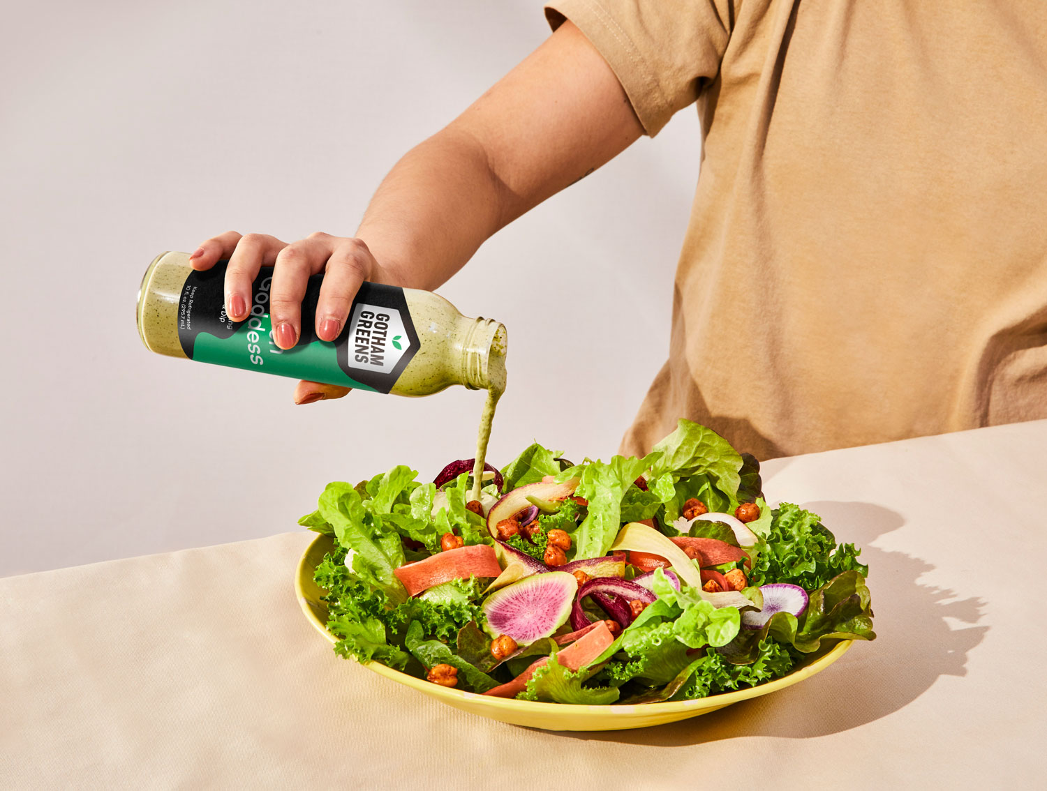 A person pouring dressing on a salad.