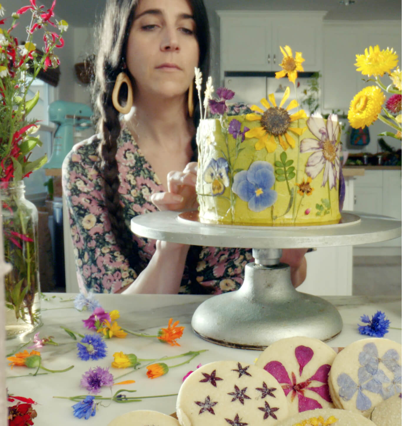 Loria Stern decorating a cake with edible flowers.