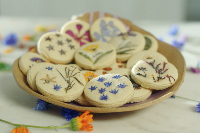Freshly baked cookies with edible flowers pressed into them