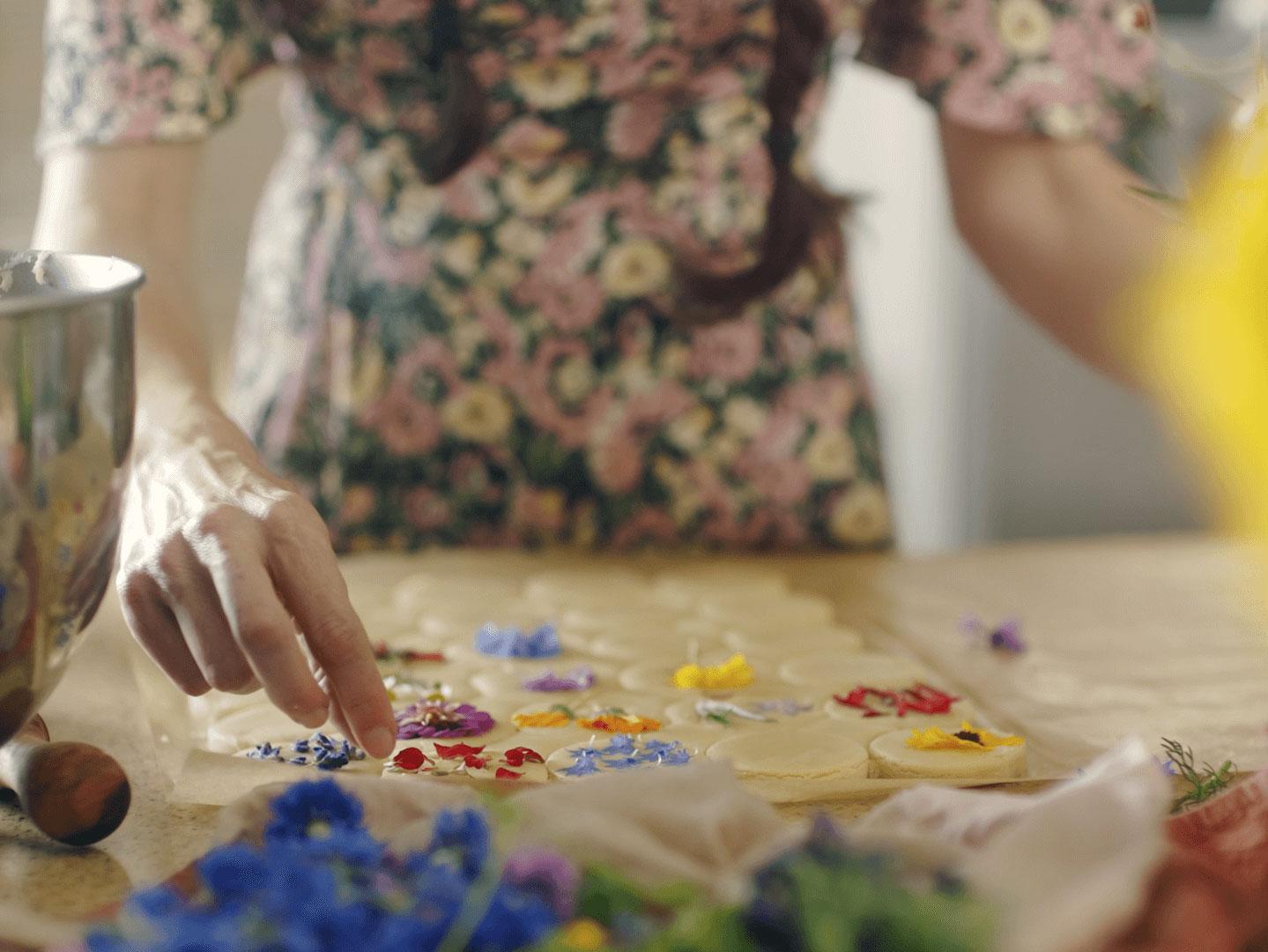 Loria Stern pressing edible flowers into cookies.