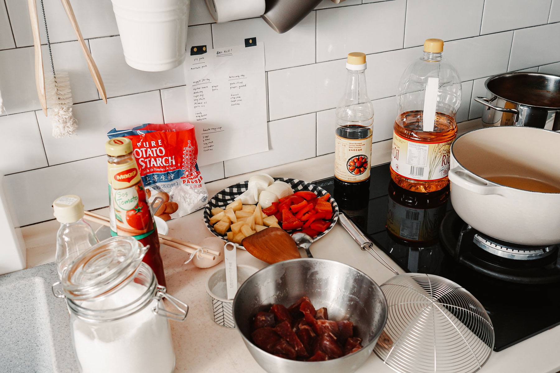 A countertop scattered with ingredients for sweet and sour pork.