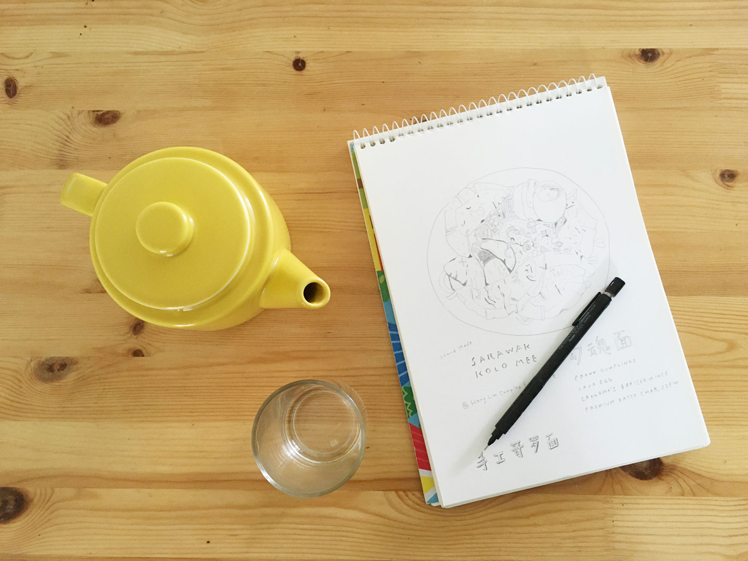 A sketch book resting on a table with a pot of tea.