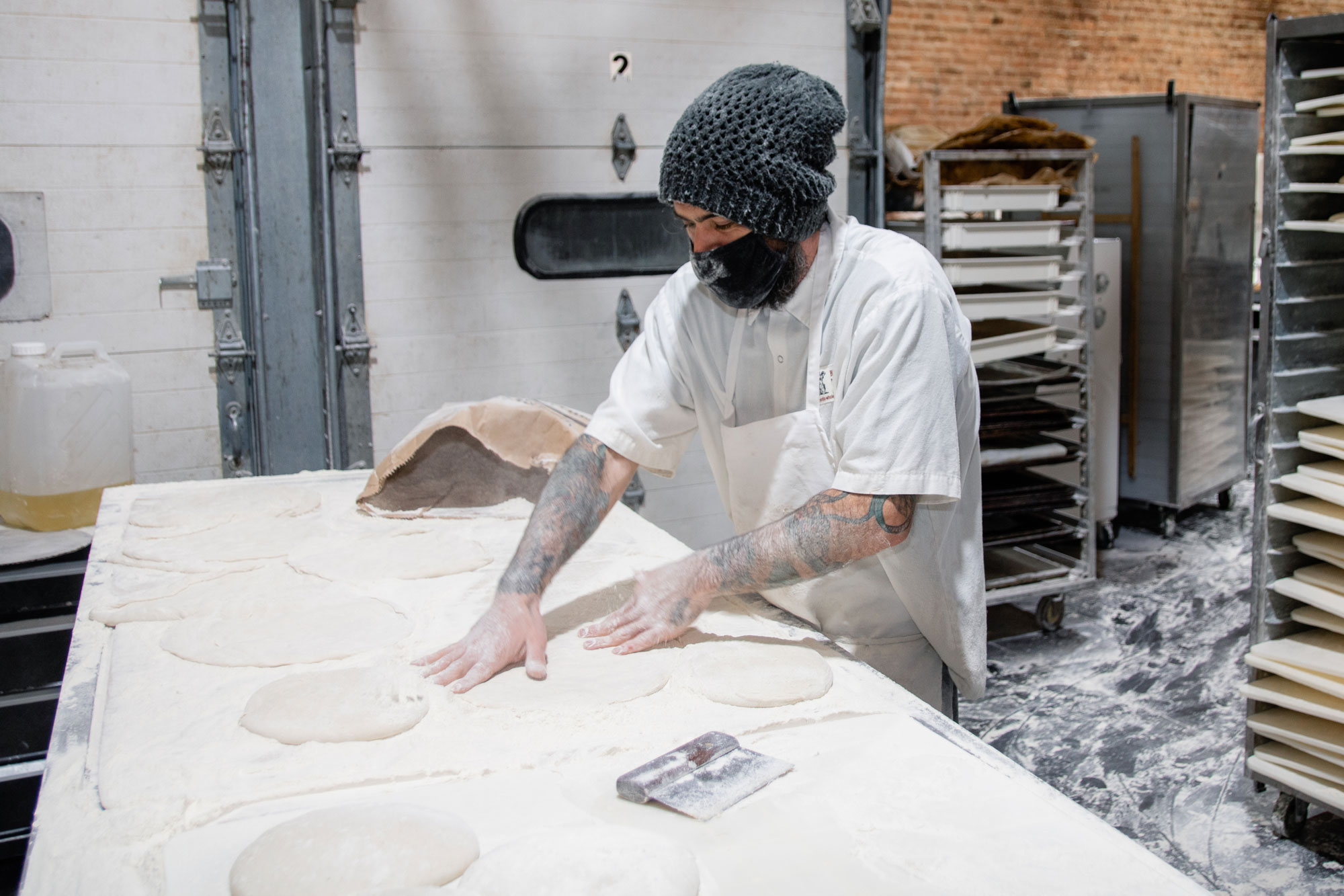 A person pressing against mounds of dough.