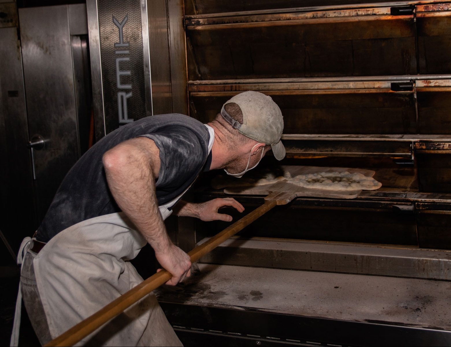 A baker placing pizzas in a large oven.