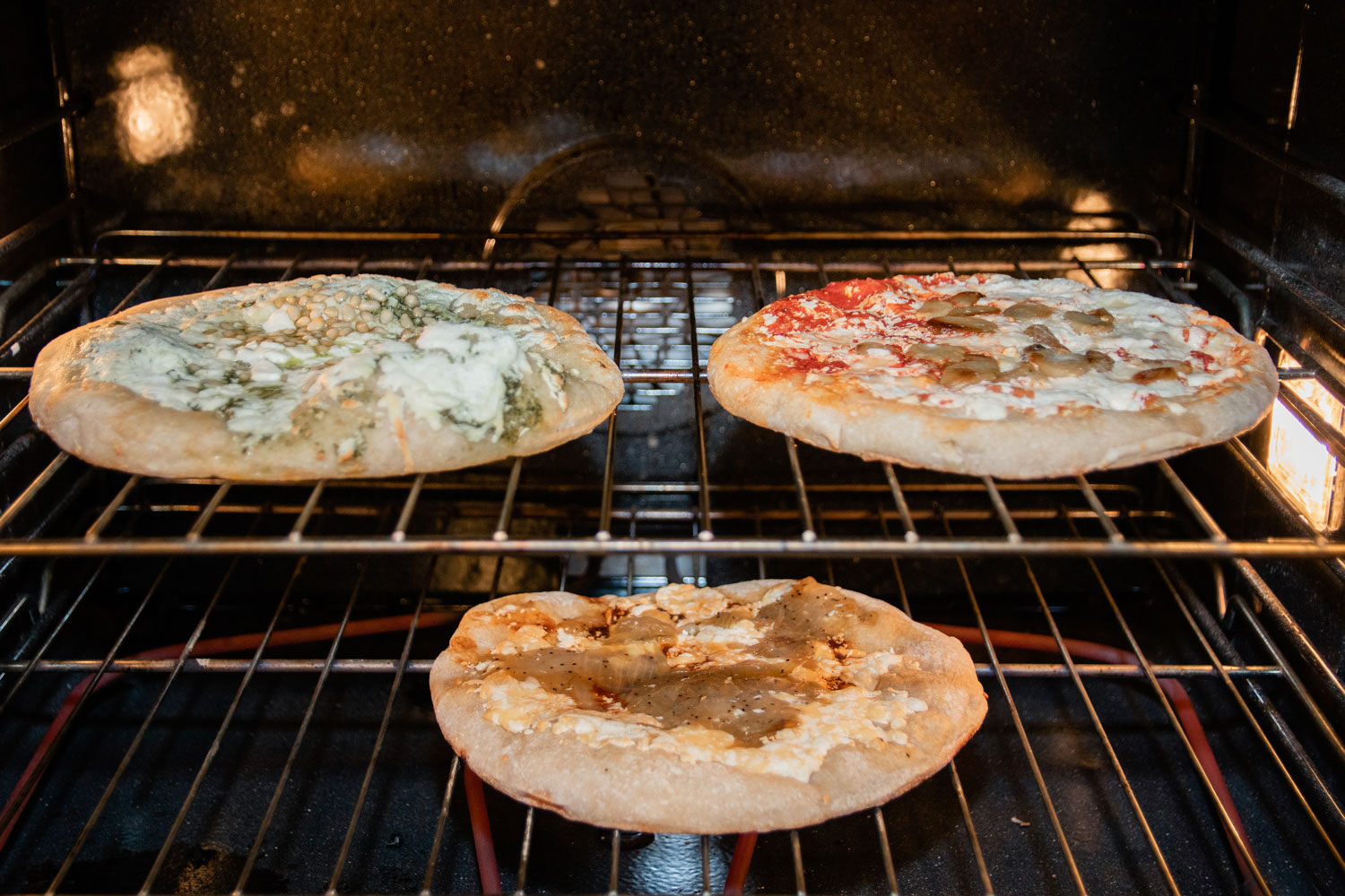 Three pizzas baking in a large oven.