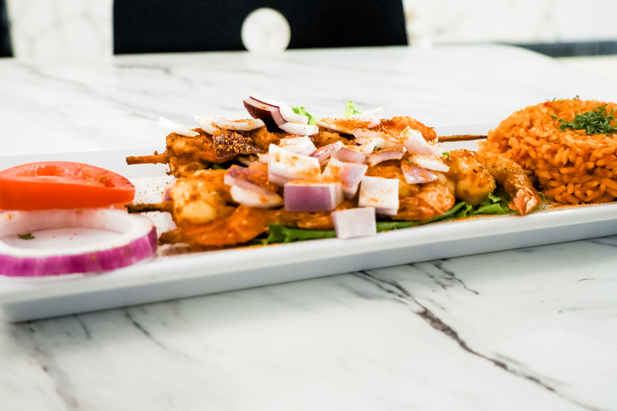 A close up of grilled shrimps on skewers.