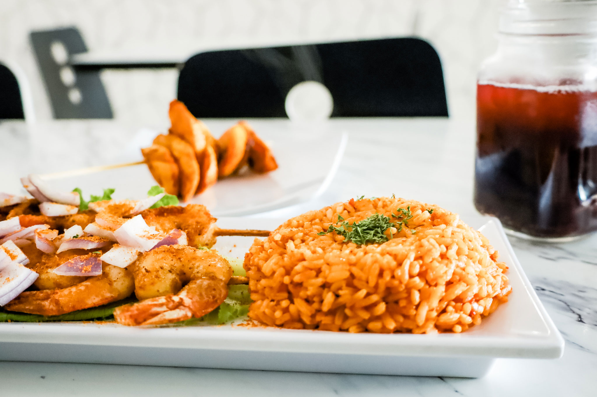 A plate of rice and grilled shrimps.