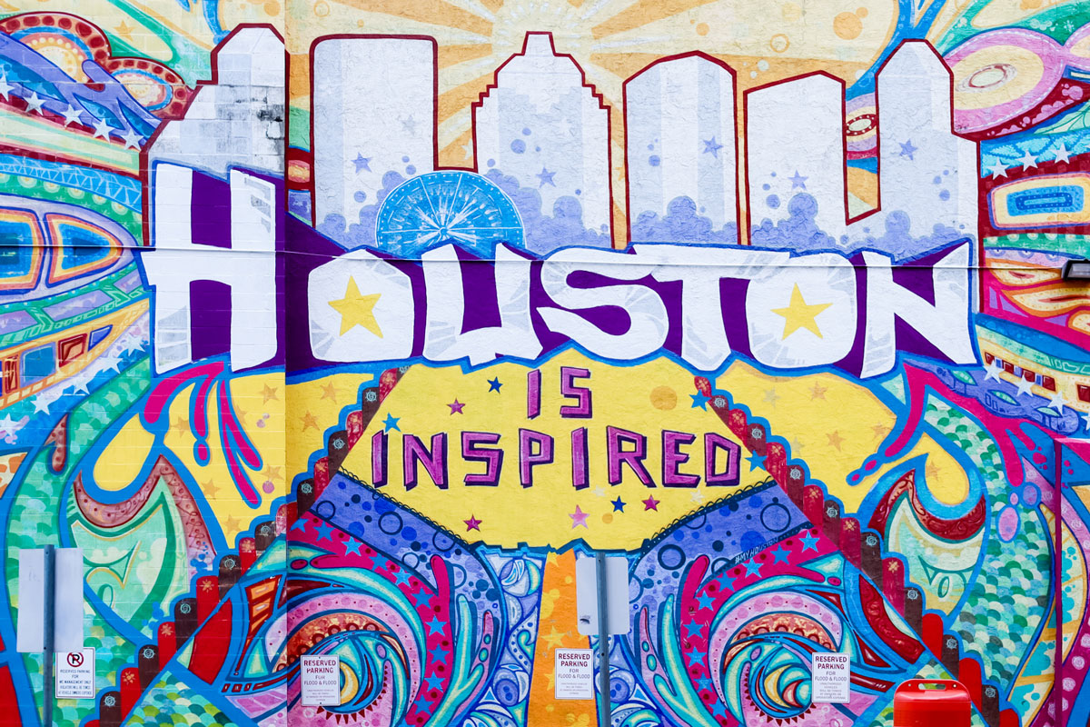 A large, colorful mural that reads Houston is inspired.