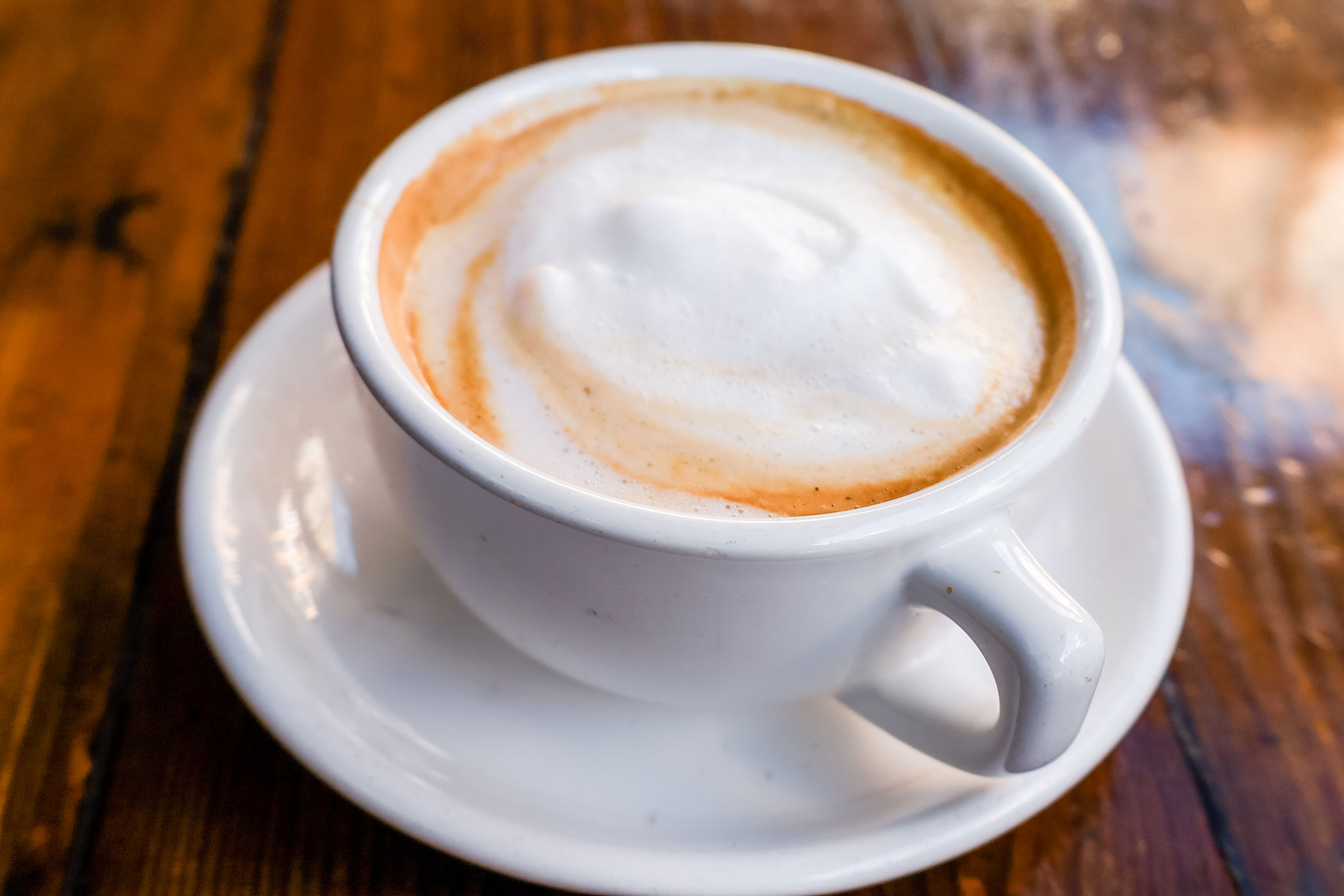 A chai tea latte in a tea cup.