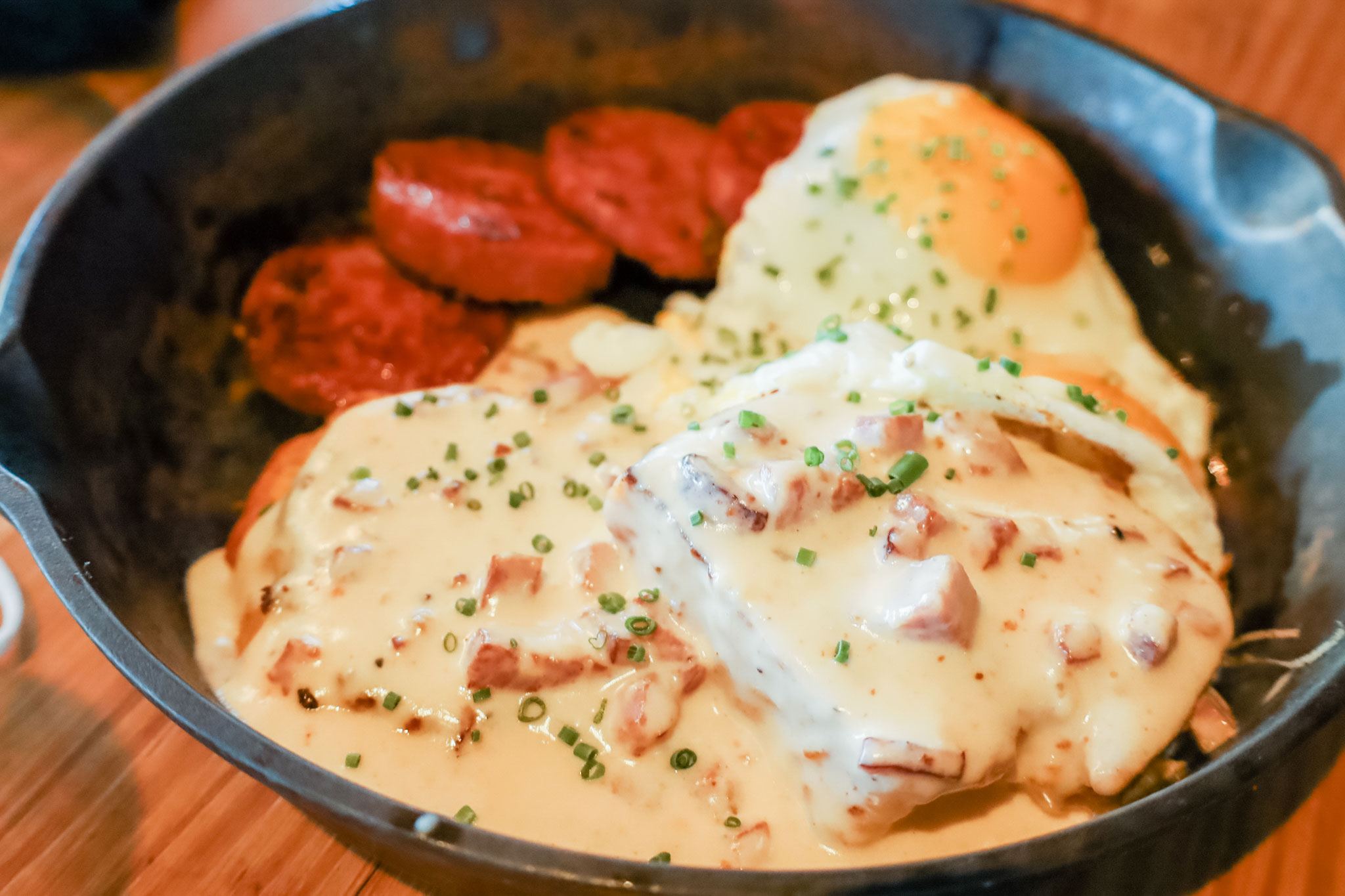 A dark bowl filled with biscuits and gravy.