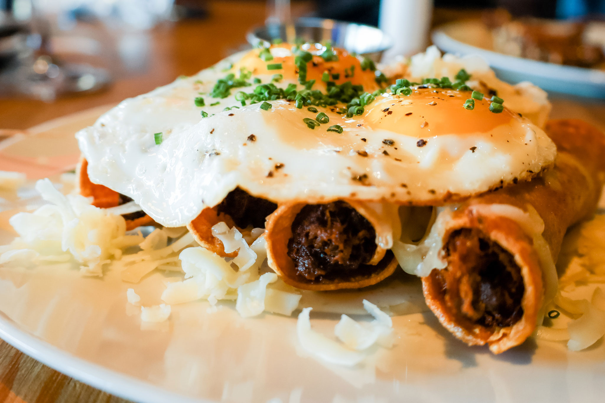A plate of taquitos topped with a fried egg.