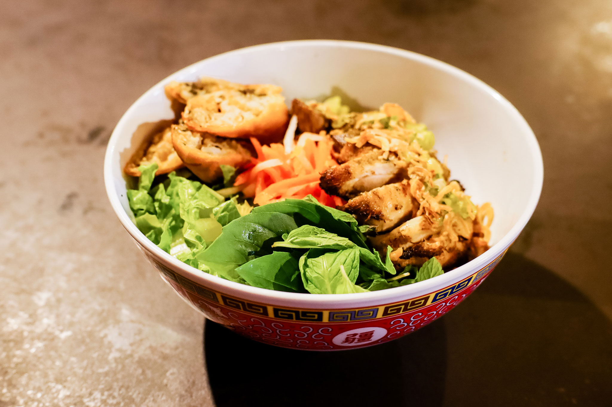 A bowl of Viatnamese noodles topped with grilled chicken.