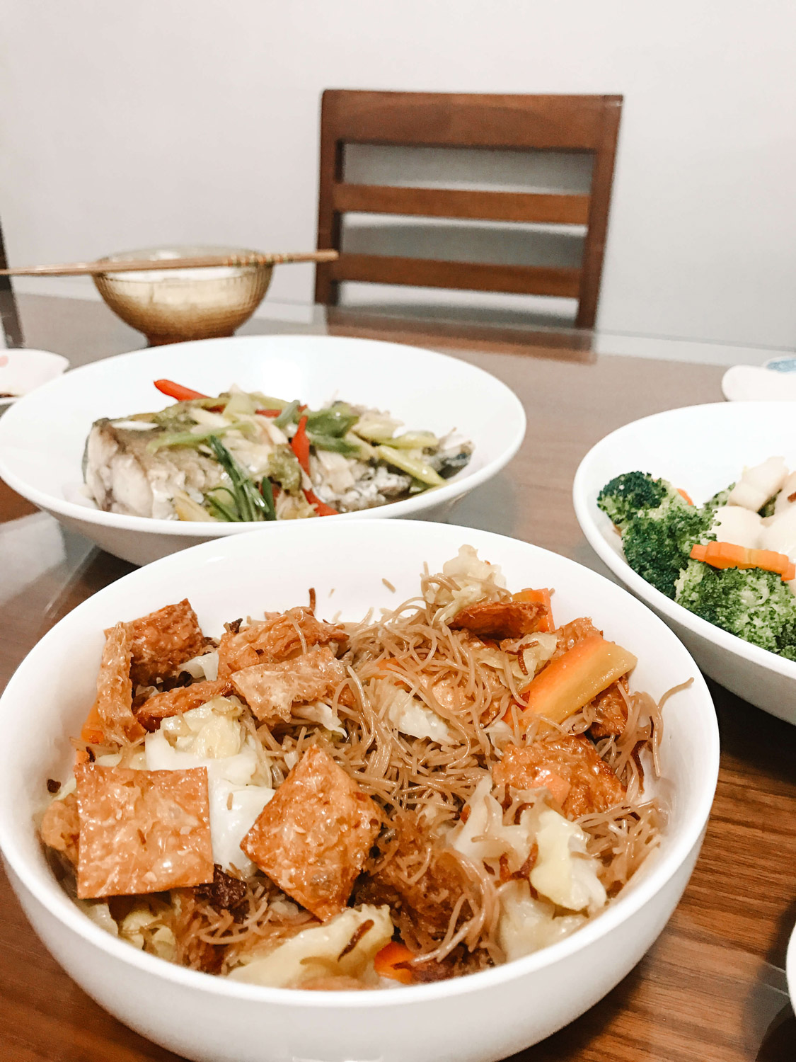 Three large serving dishes filled to the brim with food.