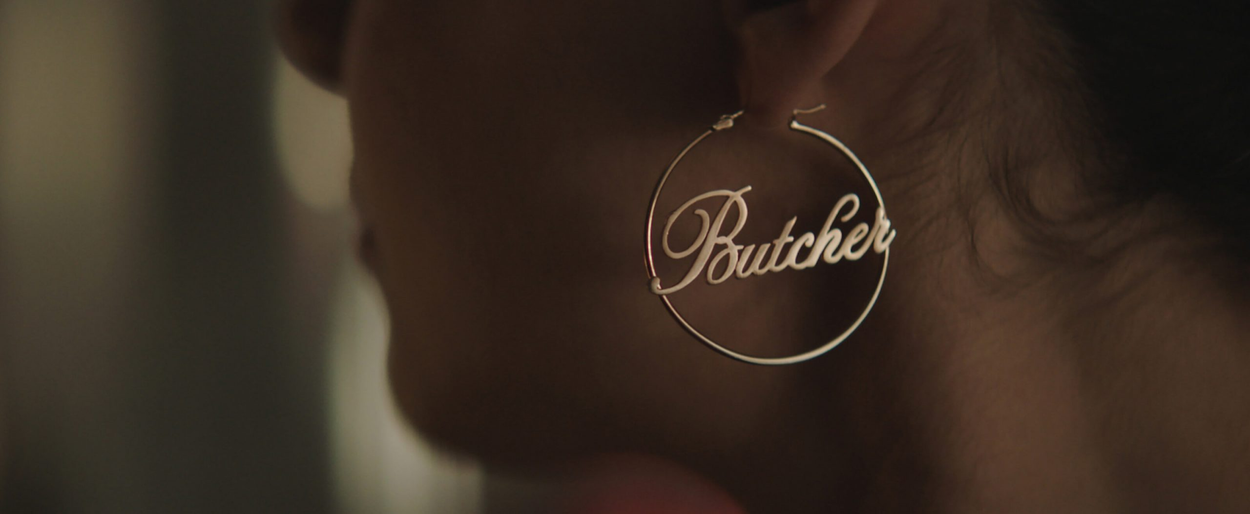 A gold hoop earring with the word Butcher spelled out in center.