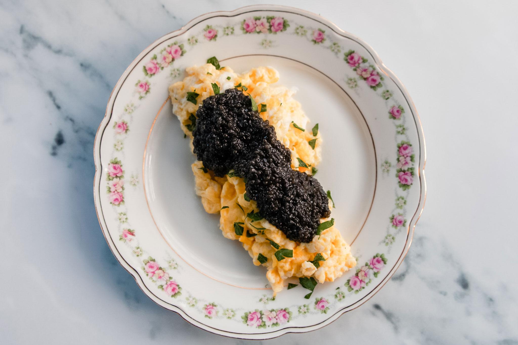 A plate of scrambled eggs topped with black caviar.