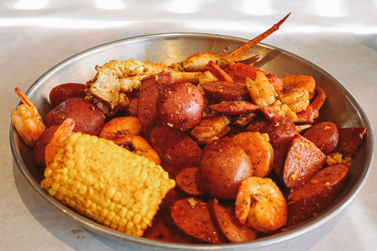 A metal bowl overflowing with a seafood boil.