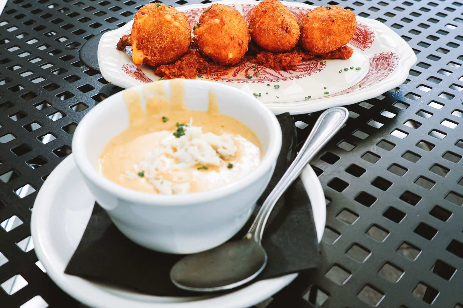 A dish of hushpuppies next to a small, delicate bowl.