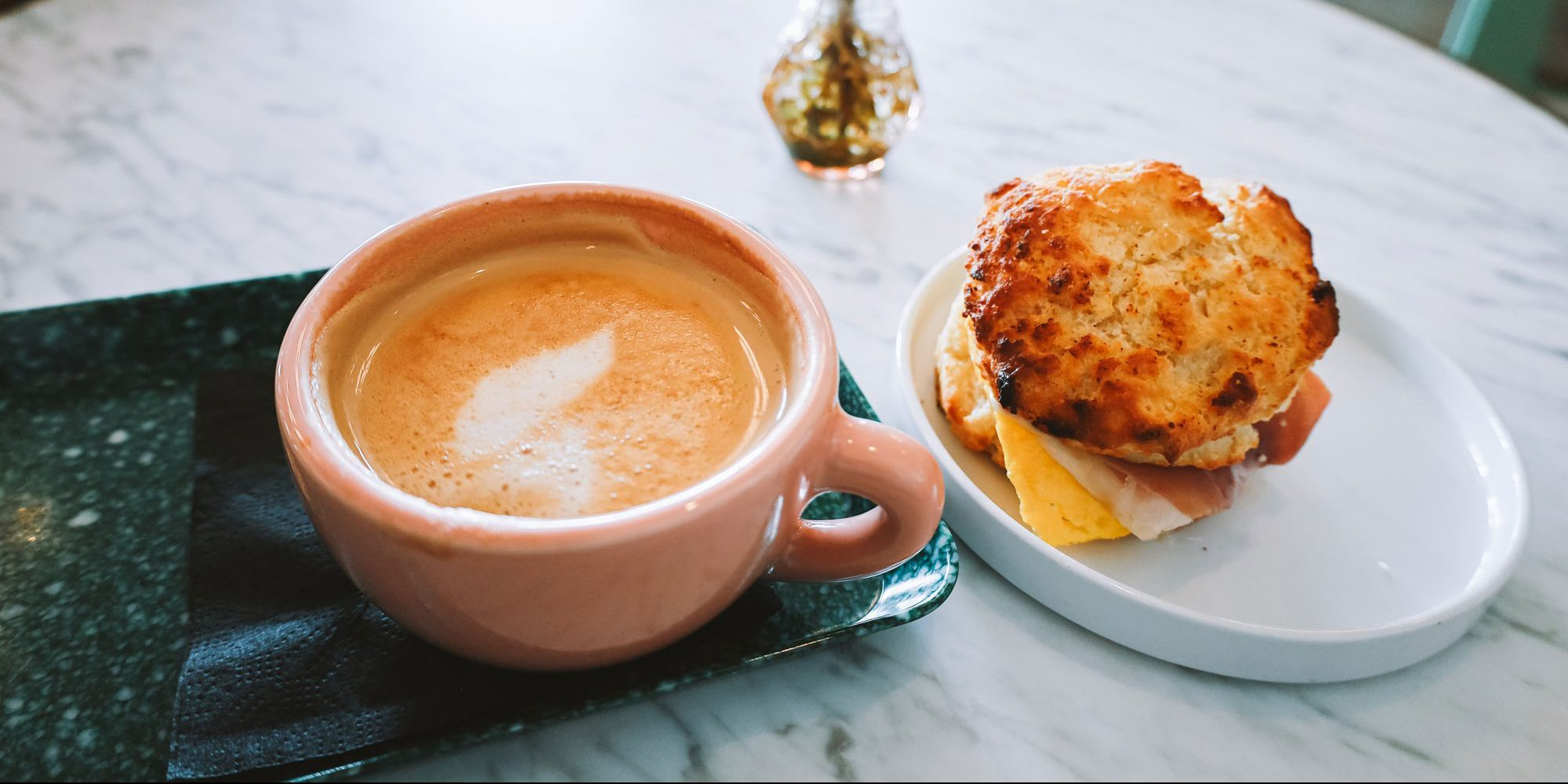 A cappuccino and a freshly made breakfast sandwich.