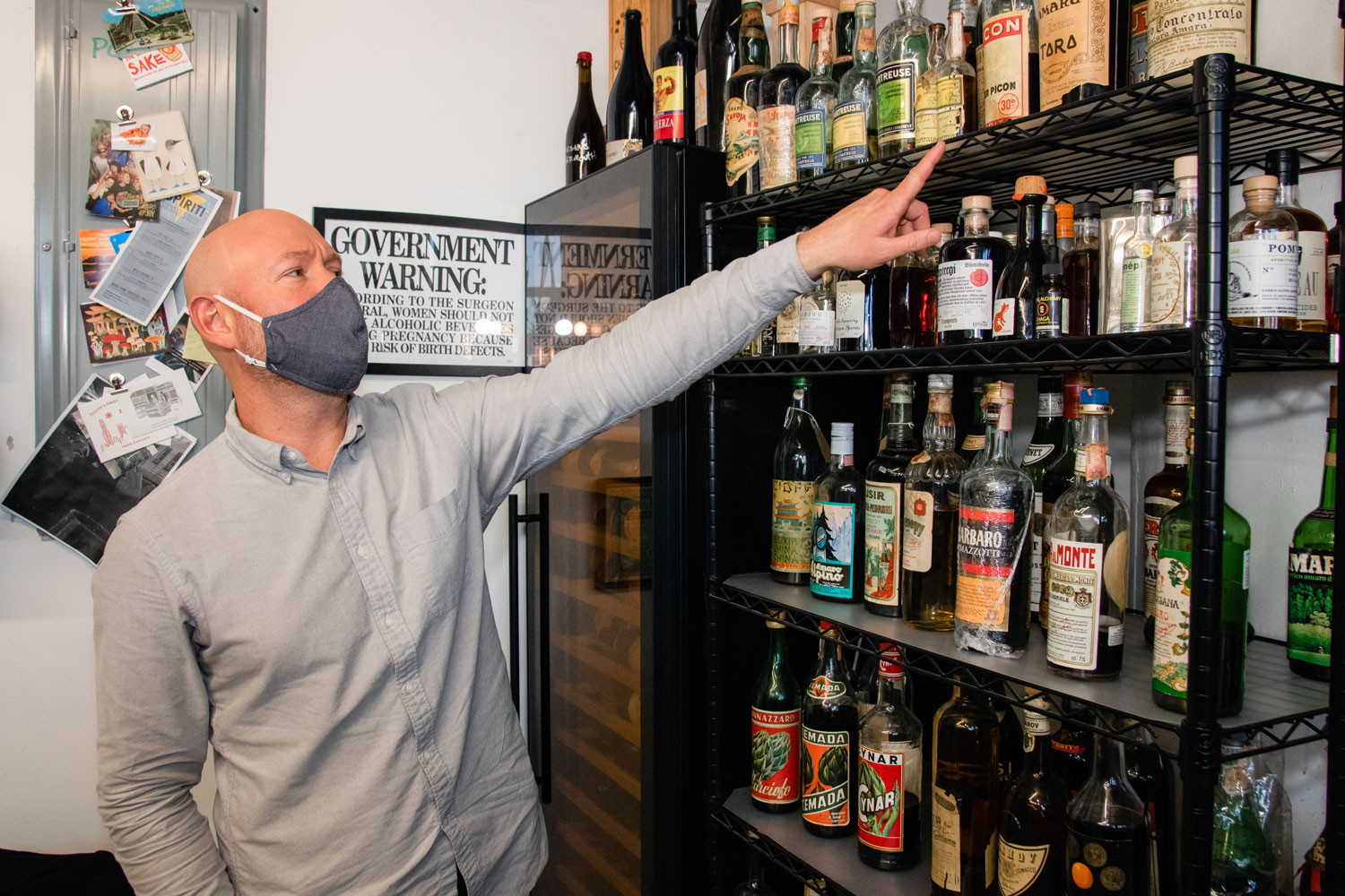 Aaron Sing Fox pointing out liquor bottles of Forthave Spirits.