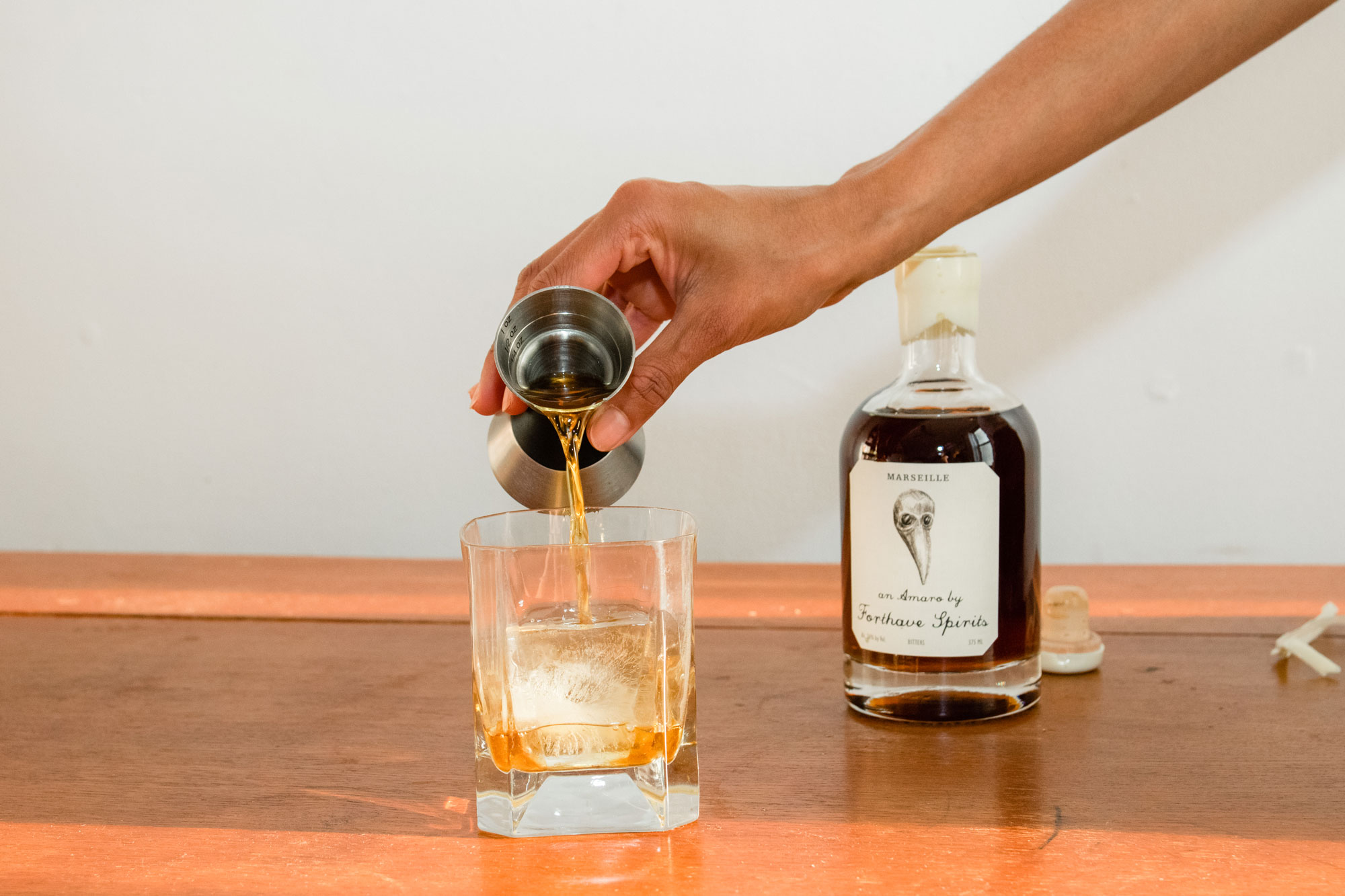 A person pouring Forthave Spirit liquor into a whiskey glass.