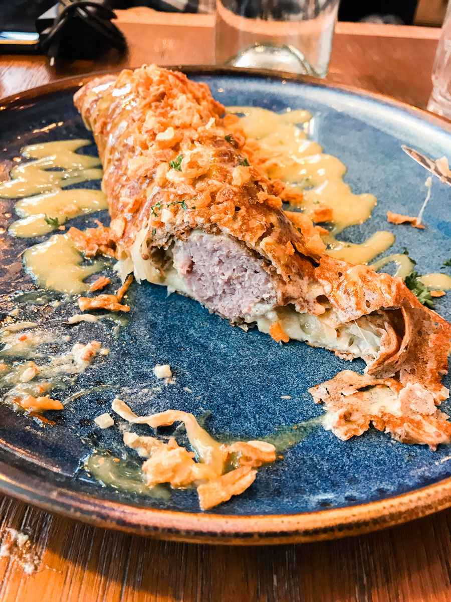 A crispy galette-saucisse drizzled in sauce.