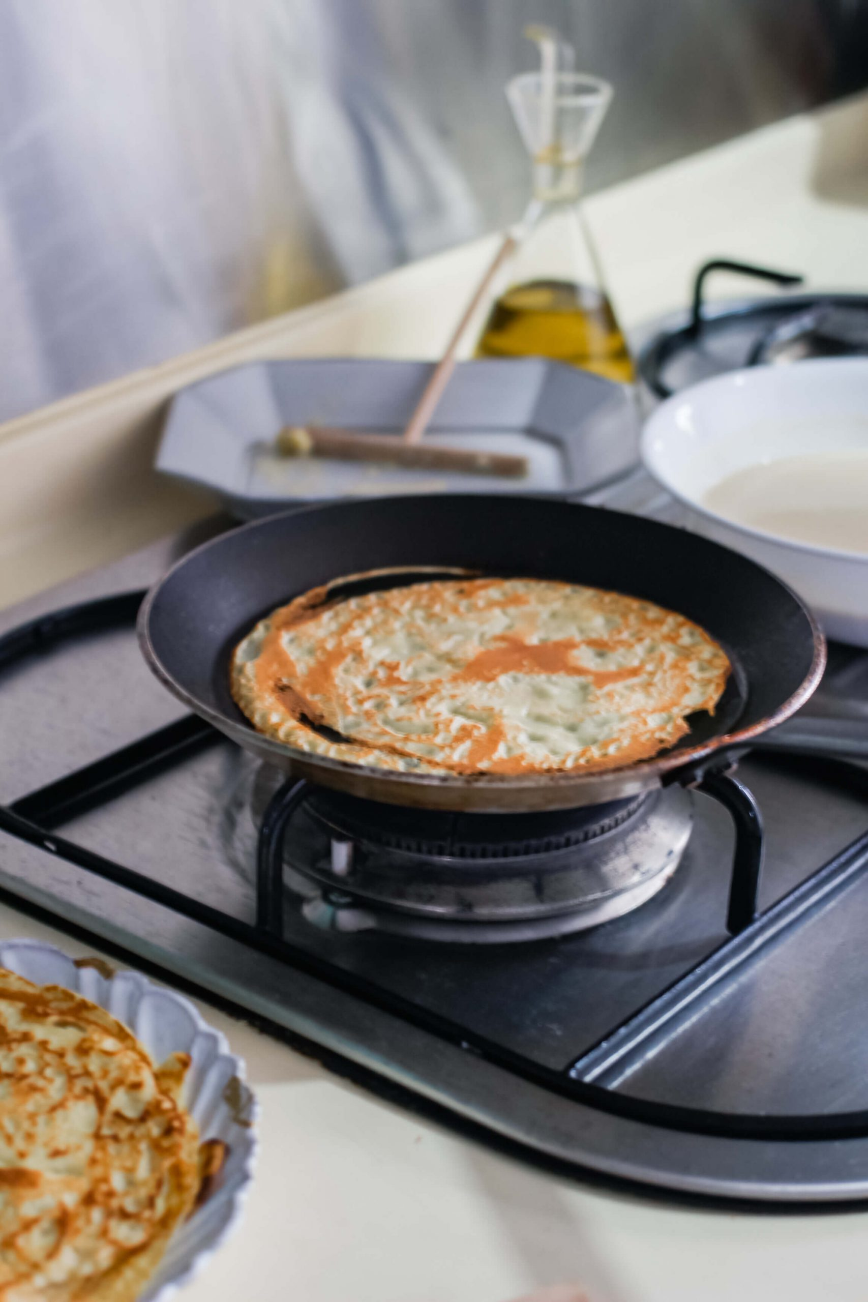 A small pan cooking a crepe.