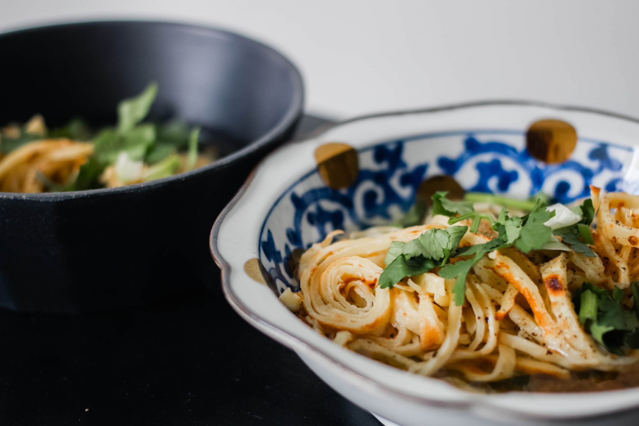 A bowl of crepe noodles in broth.