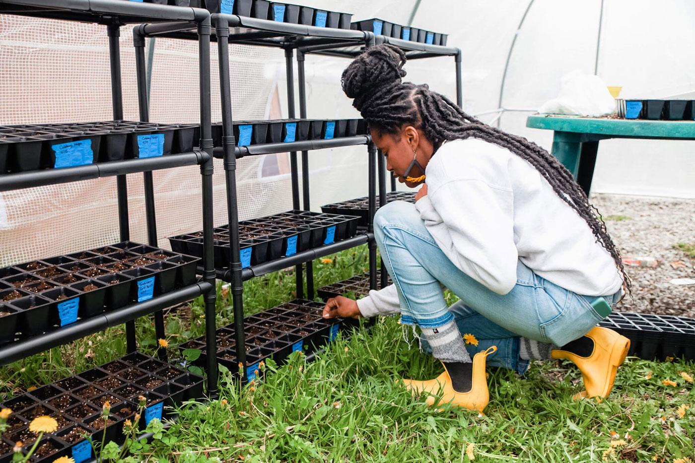 Christa tending to her nursery plants.