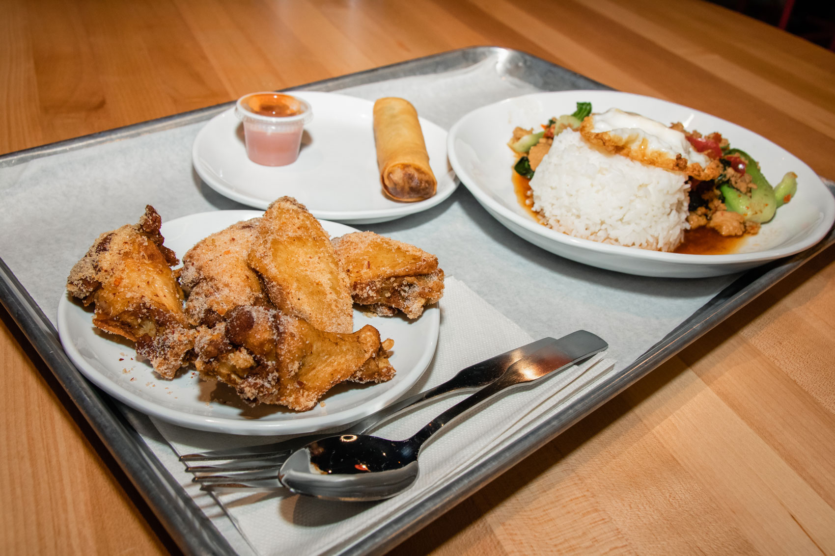 A tray of fried chicken wings and Thai food.