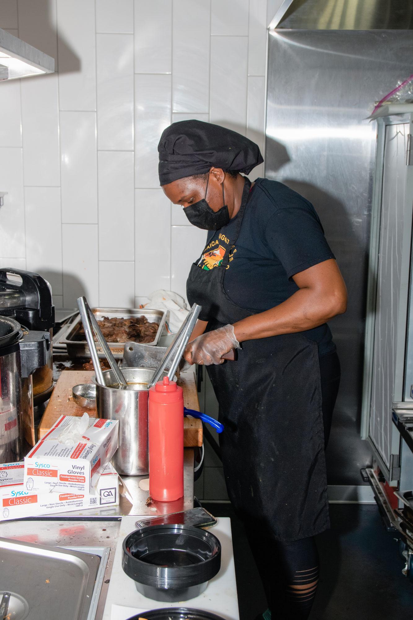 Latoya chopping meat in her kitchen.