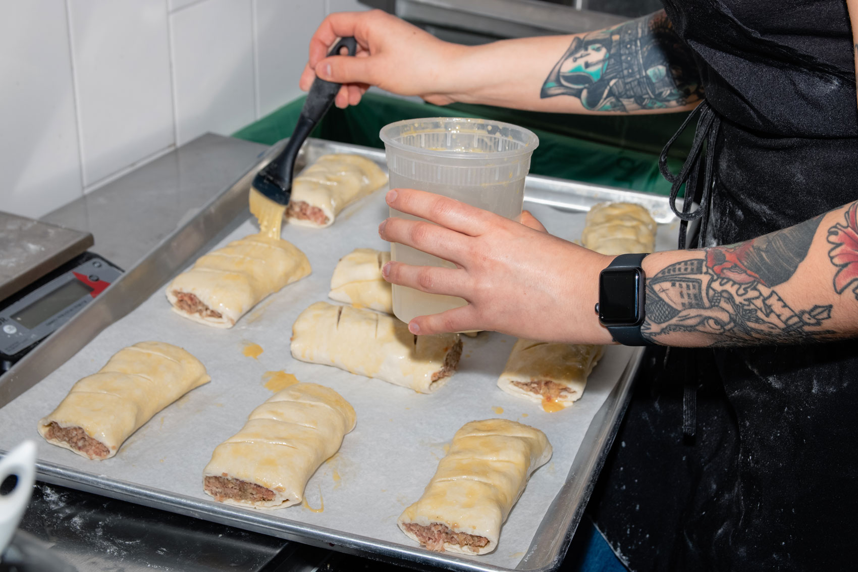 Small handheld pies being buttered.