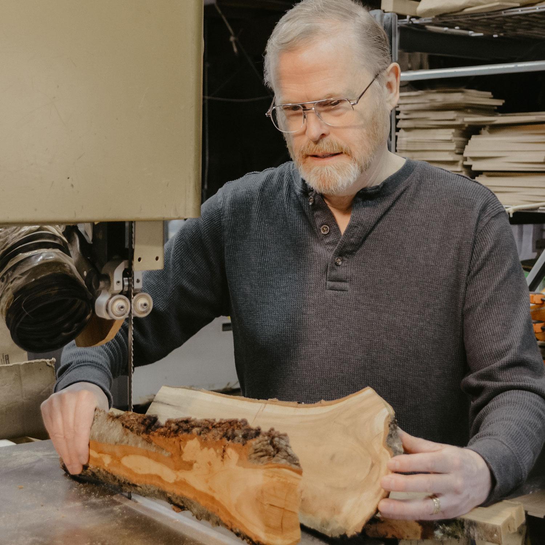 Jonathan Simons holding large pieces of wood.
