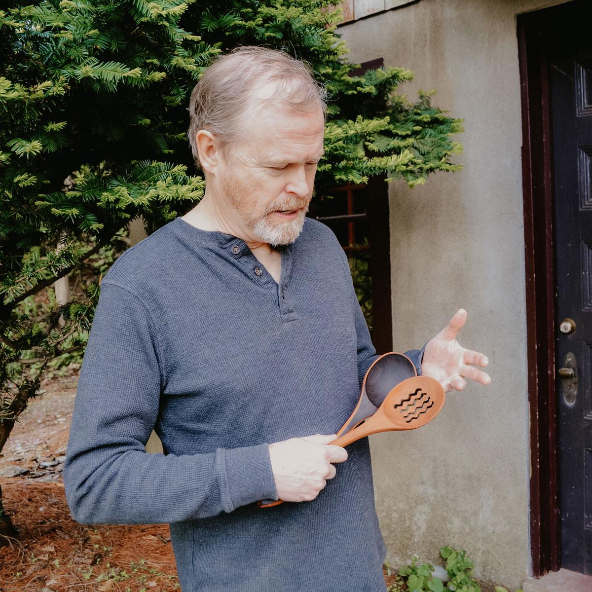 Jonathan Simons holding two wooden utensils.