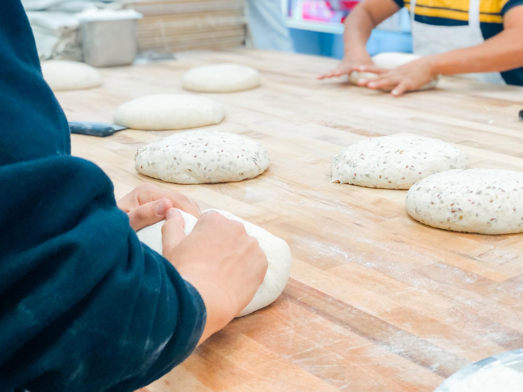 People gently making dough.