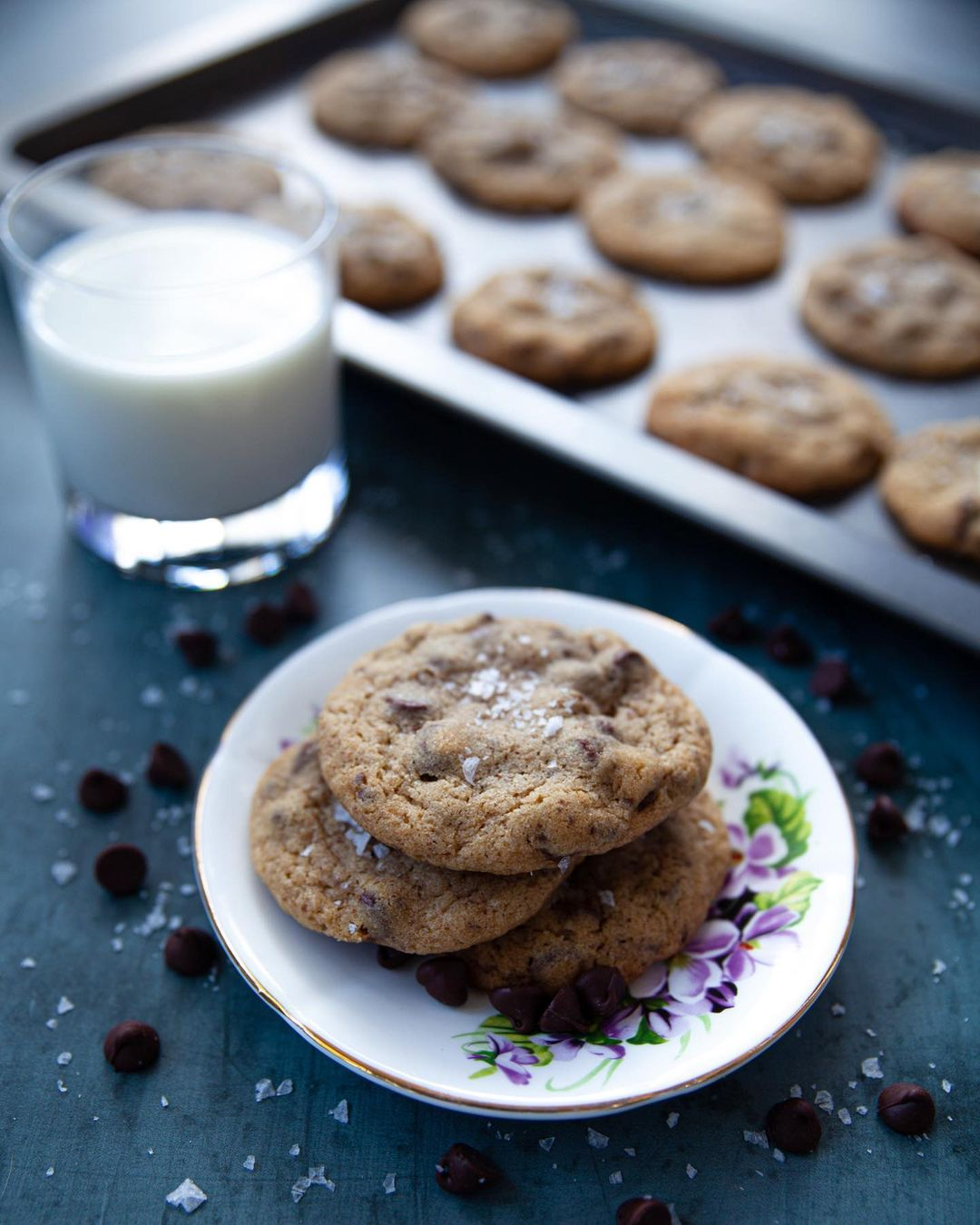 A plate of licorice cookies and a glass of milk.